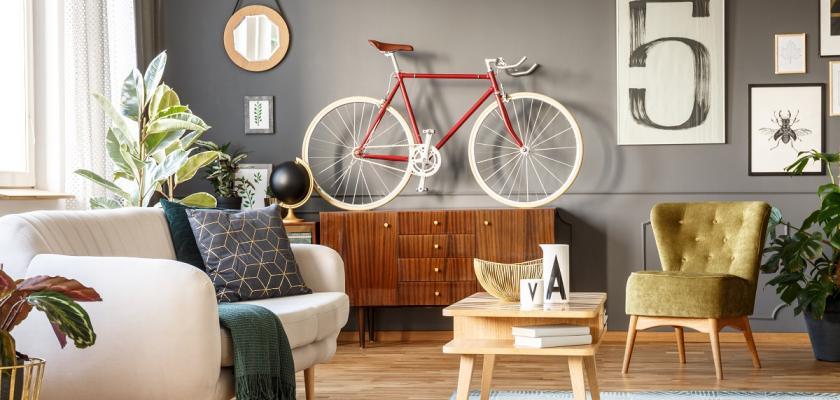 obývací pokoj se šedivou stěnou a pověšeným kolem
