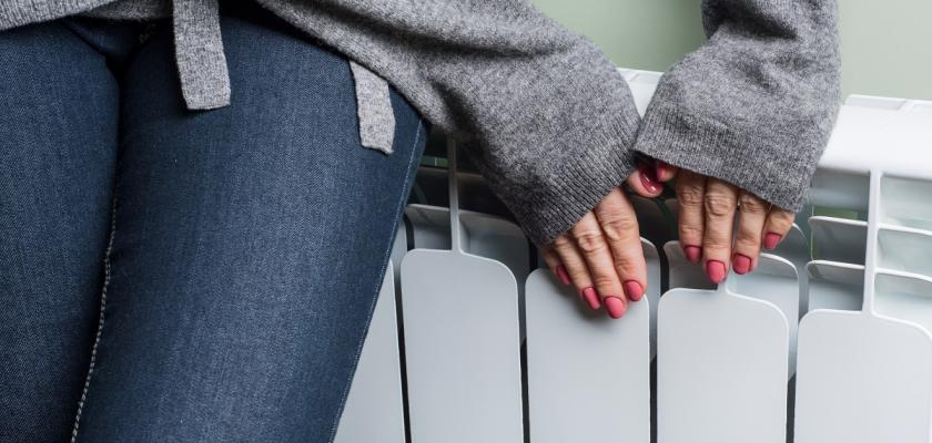 člověk zabalený do svetru sahá na radiátor