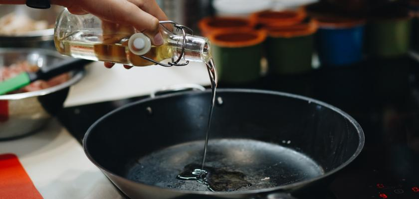 člověk nalévající olej na pánev
