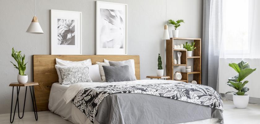 king size postel s šedivým přehozem