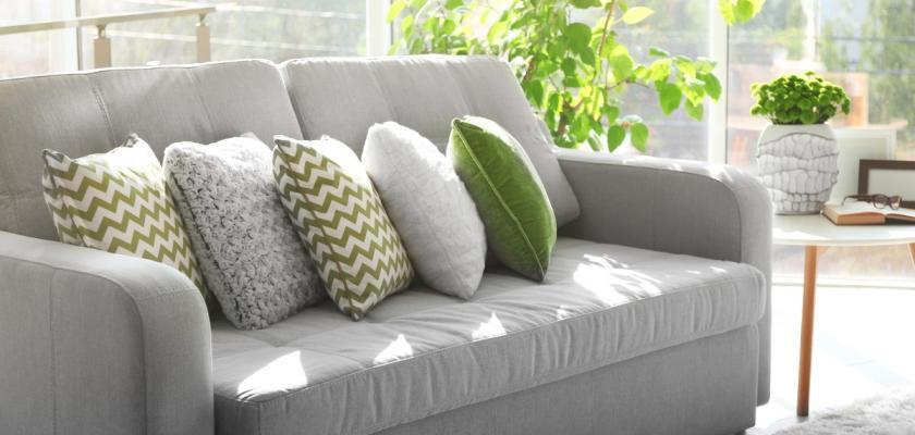 zelené a šedivé polštářky na šedivé pohovce