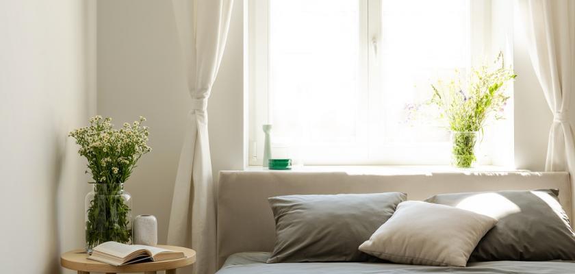 šedivá postel umístěná pod oknem