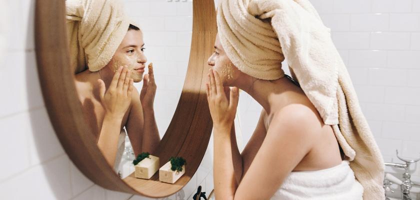 žena v turbanu stojící před zrcadlem