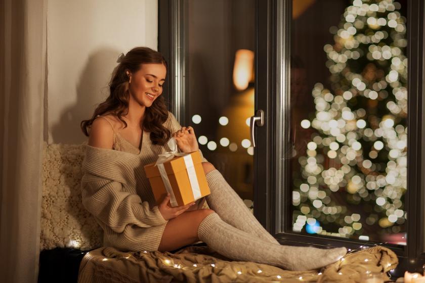 dívka s dárkem u okna