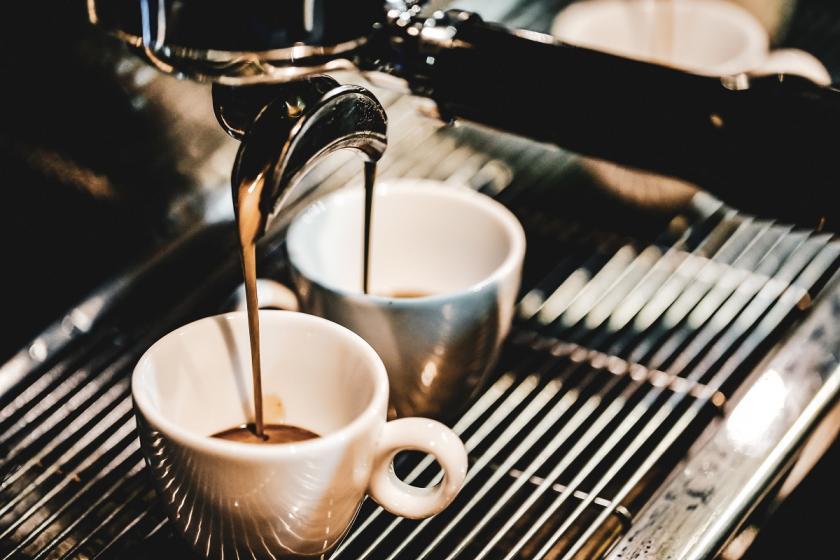 dva šálky pod kávovarem